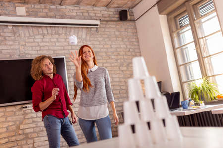 Business people having fun at the office, playing office games while on a break, tearing down a pyramid of plastic cups with a paper ball