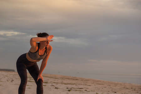 Young woman standing on the beach after an intense workout, leaning on her knees and wiping sweat after jogging down the beach early in the morning
