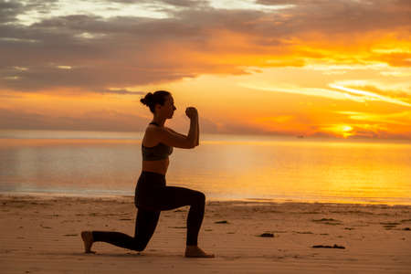 Active young woman exercising on the beach early in the morning, doing split squats and enjoying beautiful sunrise over the water