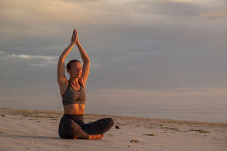 Active young woman enjoying beautiful sunrise on the beach, relaxing by practising yoga, doing seated easy yoga pose or Sukhasana with eyes closed