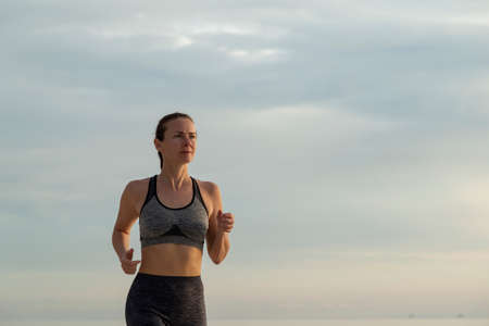 Active woman in sportswear jogging early in the morning
