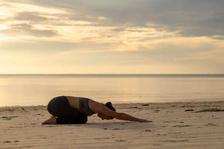 Young woman training on the beach early in the morning, practising yoga and stretching out, holding Balasana or child's pose 写真素材