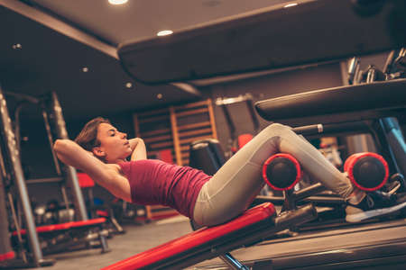 Active young woman working out in gym, doing incline bench sit ups, strengthening core and abdominal muscles