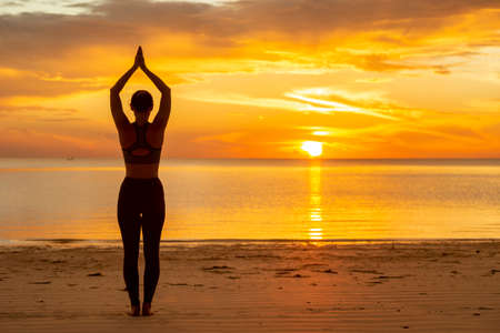 Young woman working out on the beach early in the morning, practising yoga, doing stretching out exercises, holding upward facing dog back bending yoga pose