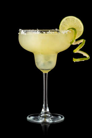 Classic lime margarita cocktail with tequila, triple sec, lime juice, crushed ice and some salt on the rim of a glass, decorated with a slice of lime isolated on white background