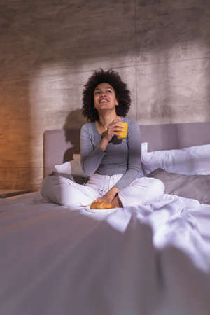 Beautiful young mixed race woman wearing pajamas lying on the bed, drinking wine, reading a magazine and enjoying leisure time at home