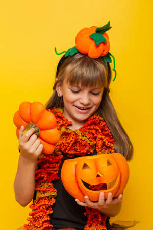 Beautiful little girl wearing Halloween costume having fun while blowing party whistle