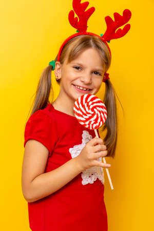 Portrait of beautiful little girl wearing deer antlers costume eating lollipop isolated on yellow colored background