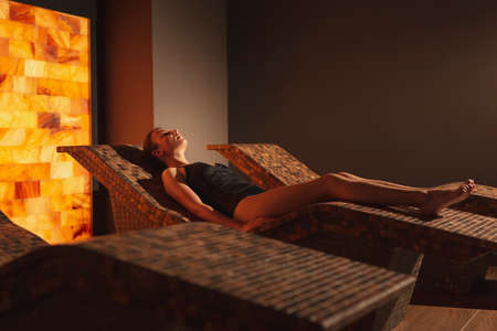 Beautiful young woman lying on a heat bed in spa center salty room, relaxing and enjoying halotherapy treatment Stock Photo