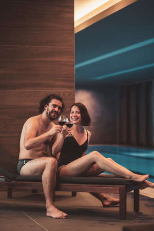 Couple in love enjoying their vacation, relaxing by the spa center swimming pool, sitting on sunbed, making a toast, raising glasses of wine towards the camera