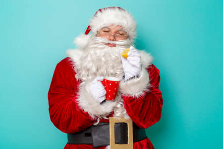 Santa Claus having fun wearing a headset, listening to the music and singing karaoke on balloon mike isolated on mint colored background