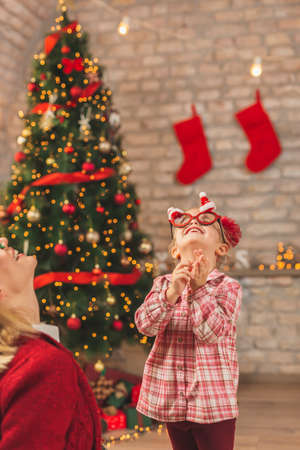 Beautiful mother and daughter sitting by nicely decorated Christmas tree, having fun at home on Christmas day, trying on Christmas party glasses