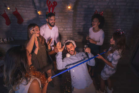 Friends having fun at New Year Eve party, making crazy faces while taking selfies together Stock Photo