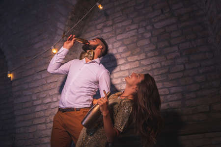 Young couple having fun at New Year's Eve party, singing, dancing and drinking champagne at midnight countdown; couple partying and drinking in nightclub