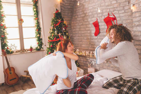 Young couple in love wearing pajamas lying in bed upside down with legs up on Christmas morning, cuddling and enjoying leisure time at home Stock Photo