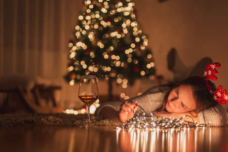 Young woman enjoying leisure time at home during winter holiday season, lying on the living room floor next to a nicely decorated Christmas tree, arranging Christmas lights Stock Photo
