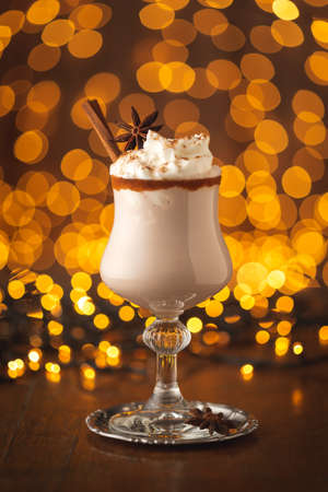 Delicious creamy homemade eggnog served in glasses with cinnamon rim decorated with anise star and cinnamon sticks - traditional winter holidays cocktail Stock Photo