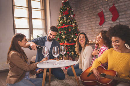 Group of friends sitting by nicely decorated Christmas tree, celebrating Christmas at home, playing the guitar, drinking wine and singing Christmas songs