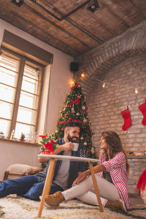 Beautiful young couple in love sitting by the nicely decorated Christmas tree, celebrating Christmas at home, drinking coffee and enjoying their time together