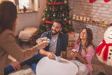 Couple spending Christmas day with friends at home, drinking coffee, eating Christmas cookies and having fun Stock Photo