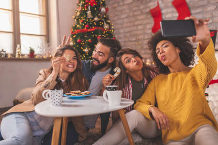 Group of friends having fun celebrating Christmas at home, making crazy faces while taking selfies