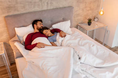 Beautiful young couple in love wearing pajams, lying in bed covered with duvet, hugging and sleeping; woman sleeping on man's shoulder