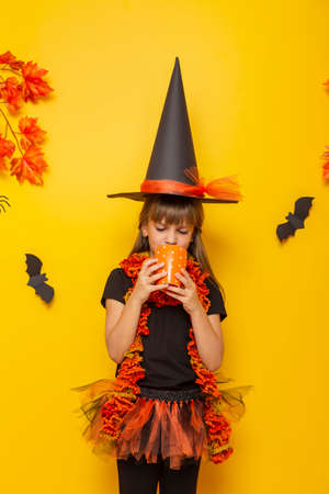 Beautiful little girl wearing witch costume for Halloween, holding a pumpkin shaped candle holder and a magic wand