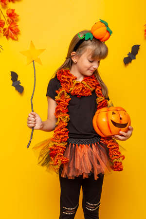 Beautiful little girl wearing witch costume for Halloween, holding a pumpkin shaped candle holder and a magic wand Standard-Bild - 157233435