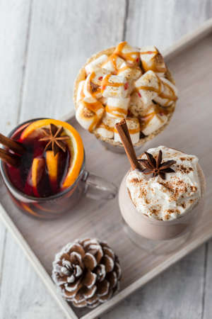 Glass of hot chocolate with toasted marshmallows and caramel topping placed on white rustic wooden tray with chocolate chip cookies Standard-Bild - 157444898