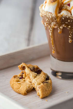 Glass of hot chocolate with toasted marshmallows and caramel topping placed on white rustic wooden tray with chocolate chip cookies