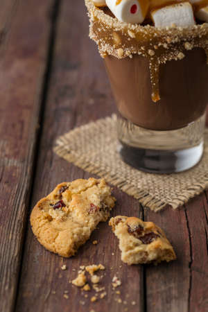 Glass of hot chocolate with toasted marshmallows and caramel topping placed on white rustic wooden tray with chocolate chip cookies Standard-Bild - 157444856