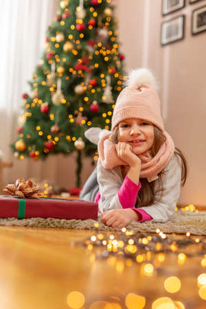 Beautiful little girl wearing costume reindeer antlers sitting next to nicely decorated Christmas tree, holding nicely wrapped Christmas present Standard-Bild