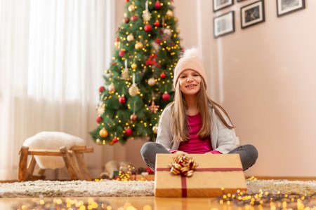 Beautiful little girl wearing costume reindeer antlers sitting next to nicely decorated Christmas tree, holding nicely wrapped Christmas present Standard-Bild - 157462393