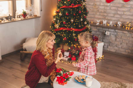 Mother and daughter having fun at home while celebrating Christmas, sitting by nicely decorated Christmas tree, making wishes for presents from Santa and playing