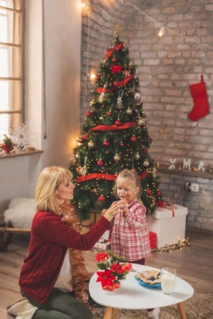 Mother and daughter having fun at home while celebrating Christmas, sitting by nicely decorated Christmas tree, making wishes for presents from Santa and playing Standard-Bild - 157473026