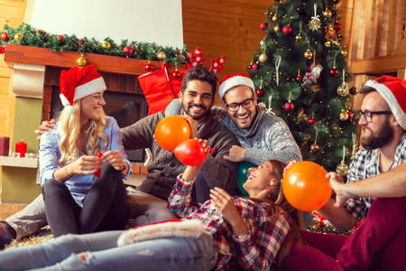Top view of group of friends sitting next to a fireplace and Christmas tree, having fun on Christmas morning, taking a selfie while blowing colorful balloons and decorating the house Standard-Bild - 157476563