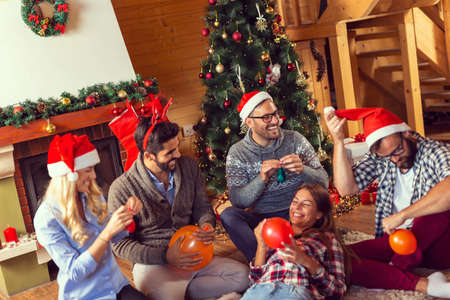 Top view of group of friends sitting next to a fireplace and Christmas tree, having fun on Christmas morning, taking a selfie while blowing colorful balloons and decorating the house Standard-Bild