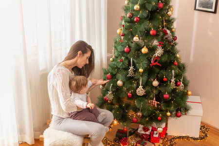 Mother holding her son in her arms and having fun while decorating his first Christmas tree
