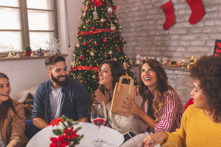 Group of friends having fun while celebrating Christmas at home, sitting by nicely decorated Christmas tree and exchanging gifts