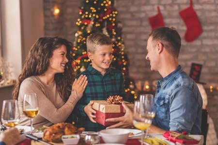 家族は家でクリスマスディナーをして、テーブルの周りに集まり、一緒に時間を楽しみました。息子にクリスマスプレゼントを与える母と父