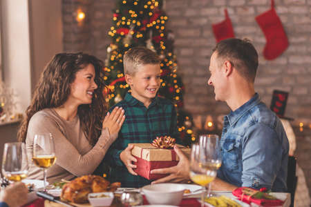 Family having Christmas dinner at home, gathered around the table, enjoying their time together; mother and father giving Christmas present to their son