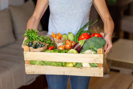 Detail of woman holding a bowl and picking out fresh organic vegetables for lunch from a food delivery wooden crate