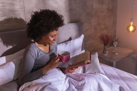Beautiful young mixed race woman wearing pajamas lying in bed in the morning, reading a book and drinking tea