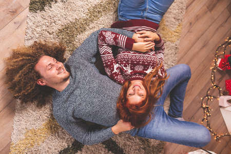 Beautiful young couple in love lying on the floor next to nicely decorated Christmas tree, having fun celebrating Christmas together at home, blowing party whistles