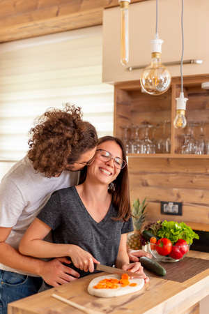 Beautiful young couple in love dancing and kissing in the kitchen, boyfriend lifting and hugging his girlfriend, having fun and relaxing at home