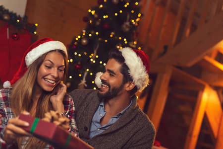 Couple sitting by nicely decorated Christmas tree, hugging, exchanging presents and having fun while celebrating New Year alone at home Stockfoto