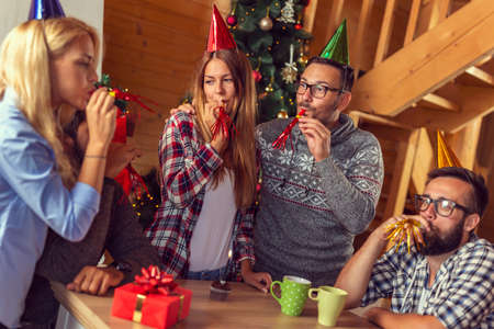 Group of friends sitting by nicely decorated Christmas tree, having fun while celebrating Christmas and friend's birthday at home, blowing party whistles