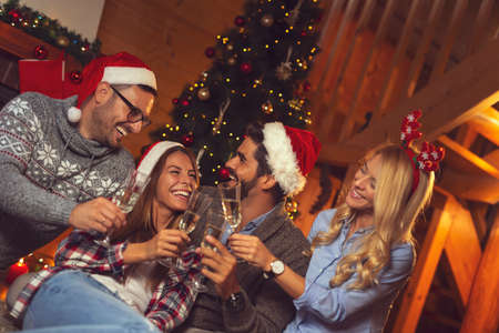 Group of friends sitting on the floor next to nicely decorated Christmas tree, making a toast with glasses of champagne at New Year's Eve midnight countdown