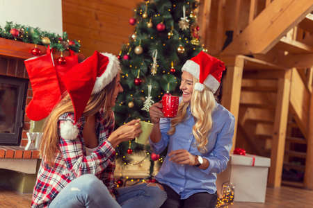 Two women sitting on the living room floor next to nicely decorated Christmas tree, drinking coffee and having fun at home on Christmas morning