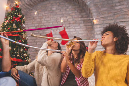 Group of young friends sitting by nicely decorated Christmas tree, celebrating Christmas at home, having fun while exchanging and opening presents 版權商用圖片